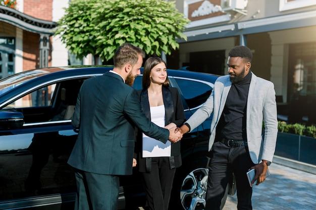 Dos hombres guapos, africanos y caucásicos, dándose la mano con una sonrisa mientras está de pie delante del coche al aire libre. bastante mujer caucásica se interpone entre ellos.