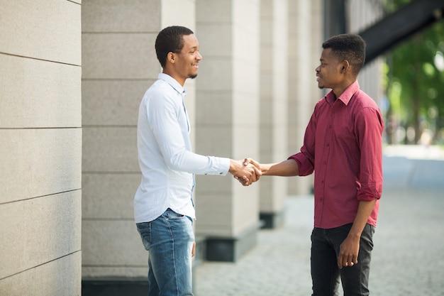 Dos hombres guapos en camisas dándose la mano