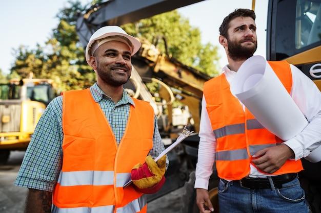 Dos hombres ingenieros discutiendo su trabajo de pie contra las máquinas de construcción
