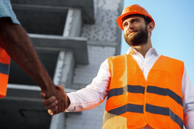 Dos hombres ingenieros en ropa de trabajo un apretón de manos contra el sitio en construcción