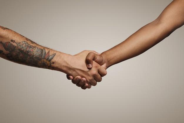 Dos hombres jóvenes de cadera se dan la mano aislado en blanco