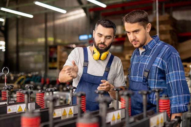 Dos hombres jóvenes comprobando nuevos equipos de procesamiento industrial mientras uno de ellos explica sus principios de funcionamiento