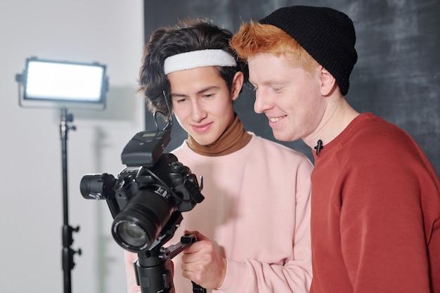 Dos hombres jóvenes felices en ropa casual viendo videos grabados en la pantalla digital de la cámara después de disparar