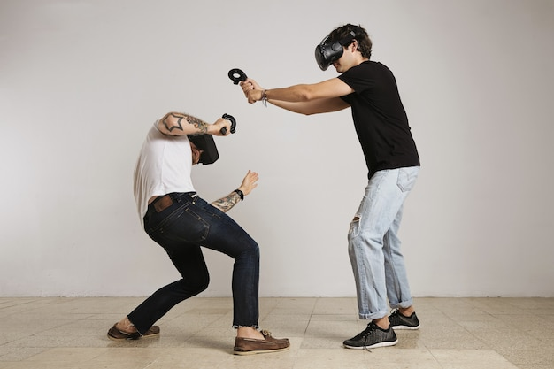 Dos hombres jóvenes con gafas de realidad virtual pelean, el hombre de camiseta negra golpea y el hombre de camiseta blanca patos y bloques
