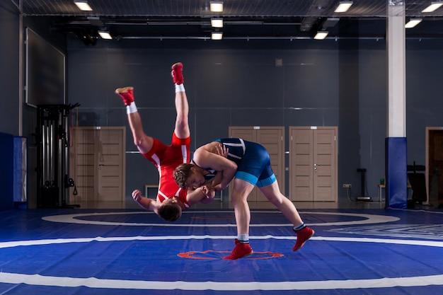 Dos hombres jóvenes con medias de lucha azules y rojas luchan y hacen una lucha suplex
