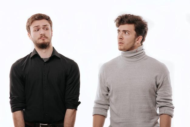 Dos hombres jóvenes, miren con desprecio, concepto de emociones, espacio en blanco aislado, espacio de copia, emociones faciales negativas