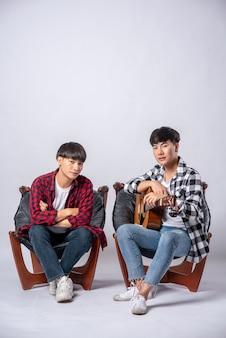 Dos hombres jóvenes sentados en una silla sosteniendo una guitarra
