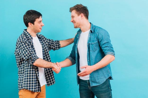 Dos hombres jóvenes sonrientes que sacuden las manos contra fondo azul