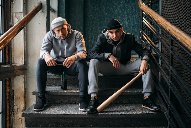 Dos hombres ladrones están sentados en las escaleras. bandidos callejeros con bate de béisbol y botella de alcohol esperando a la víctima. concepto de crimen