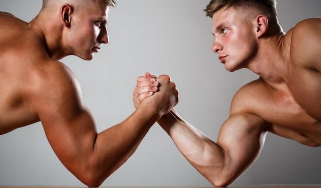 Dos hombres luchando por el brazo. rivalidad, primer plano de la lucha de brazos masculina.