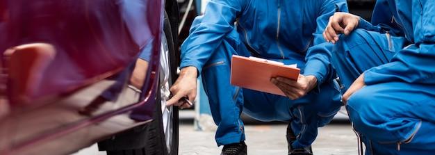 Dos hombres mecánicos comprobando el caucho de los neumáticos de coche en el garaje