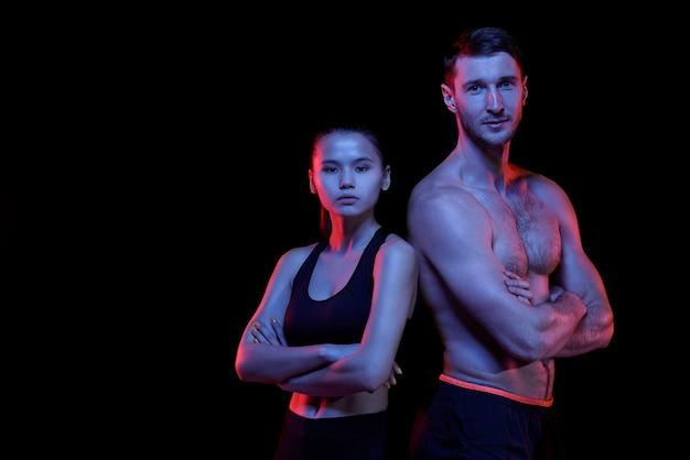 Dos hombres y mujeres jóvenes deportivos en ropa deportiva cruzando los brazos por el pecho mientras están de pie frente a la cámara de forma aislada
