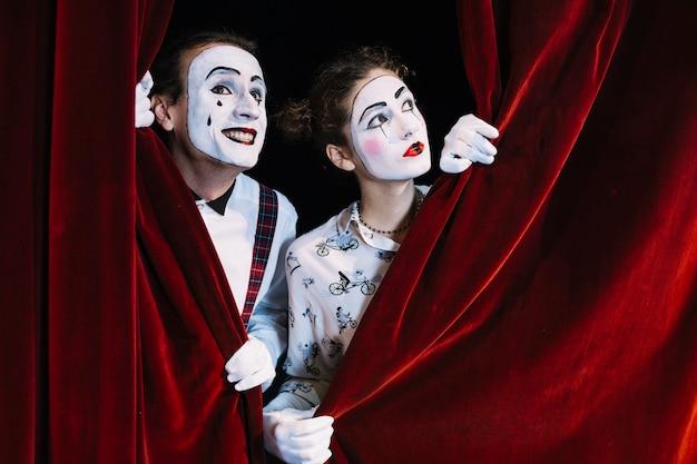 Dos hombres y mujeres mimo artista mirando a través de la cortina roja