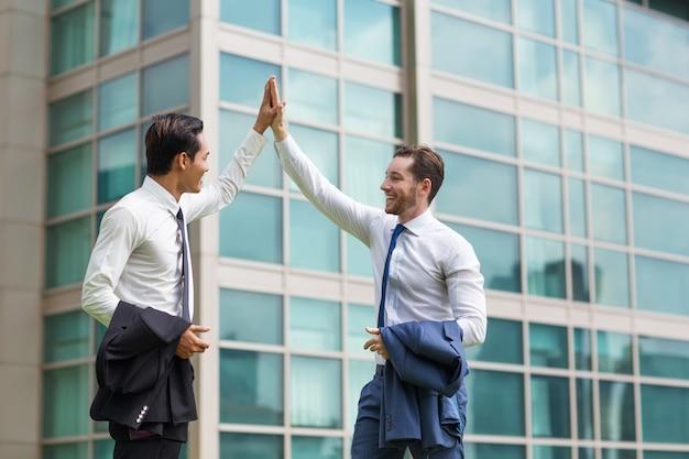 Dos hombres de negocios adultos felices fiving alto