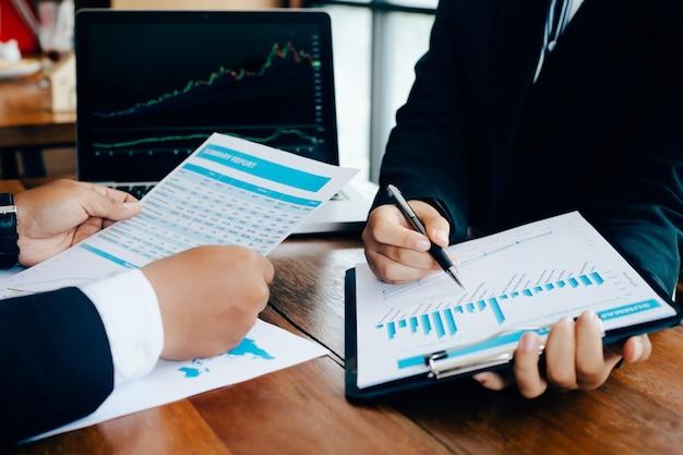 Dos hombres de negocios analizan gráfico de negocios y documentos que tienen discusión en la oficina