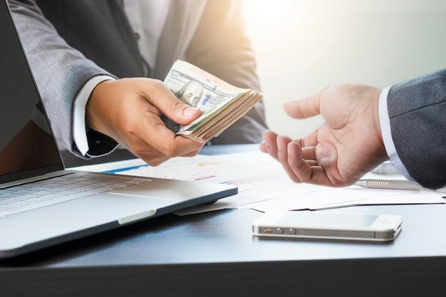 Dos hombres de negocios dan y toman billetes de dólar estadounidense. el dólar estadounidense es la moneda de cambio principal y popular en el mundo. inversión y pago