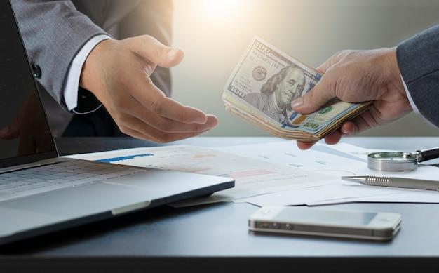 Dos hombres de negocios dan y toman billetes de dólar estadounidense.