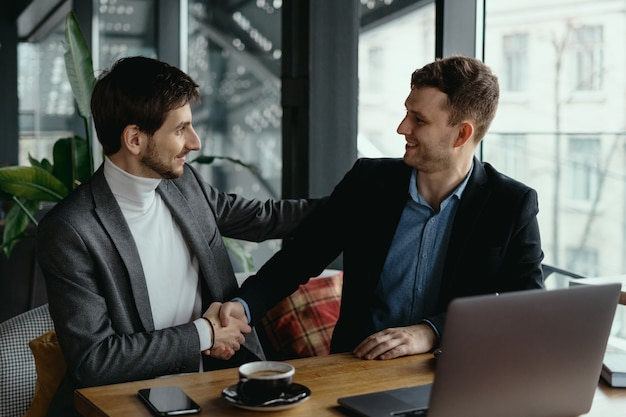 Dos hombres de negocios dándose la mano mientras se reúnen en el lobby
