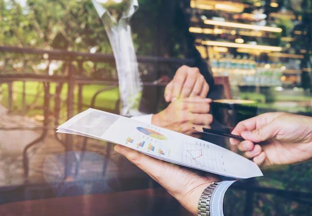 Dos hombres de negocios discutiendo su informe en la cafetería