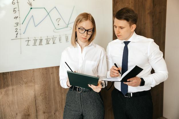 Dos hombres de negocios exitosos llenan documentos en la oficina.