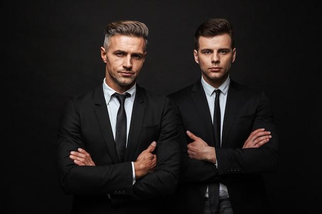 Dos hombres de negocios guapos confiados vistiendo traje que se encuentran aisladas sobre la pared negra, con los brazos cruzados