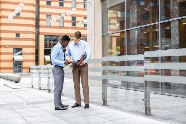 Dos hombres de negocios hablando y mirando documentos