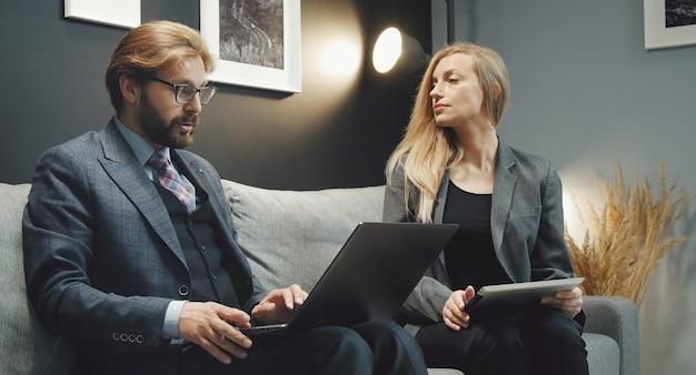 Dos hombres de negocios, hombre y mujer, discutiendo ideas sentados juntos en el sofá sosteniendo aparatos digitales