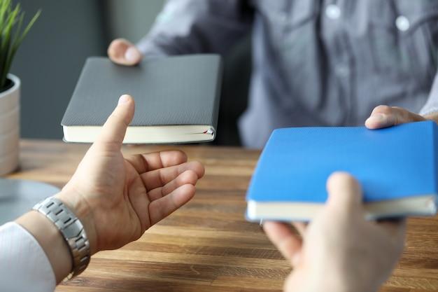 Dos hombres de negocios intercambiando cuadernos en el lugar de trabajo de la oficina