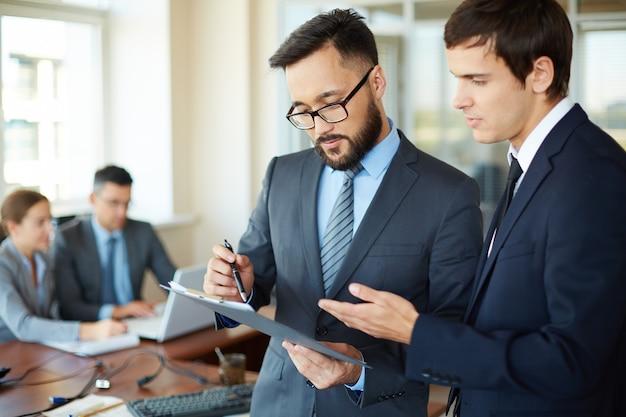 Dos hombres de negocios jóvenes con un informe