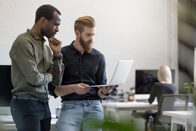 Dos hombres de negocios jóvenes preocupados mirando la computadora portátil