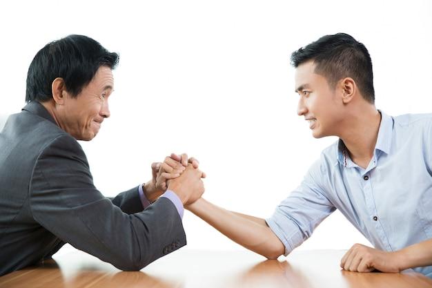 Dos hombres de negocios de lucha del brazo agresivamente