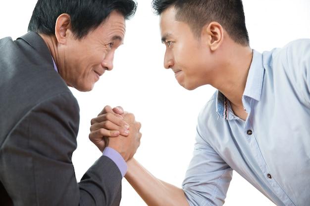 Dos hombres de negocios la lucha de brazo tercamente, primer
