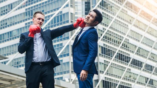 Dos hombres de negocios luchan con un guante de boxeo en una ciudad al aire libre