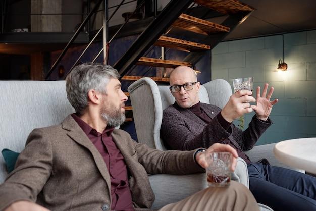 Dos hombres de negocios de mediana edad bebiendo whisky en el lounge bar y planificando una nueva campaña comercial