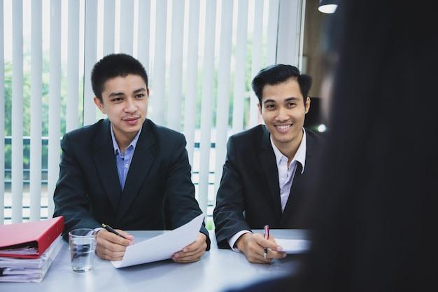 Dos hombres de negocios que escuchan las respuestas de los candidatos explicando sobre su perfil, el concepto de entrevista de trabajo