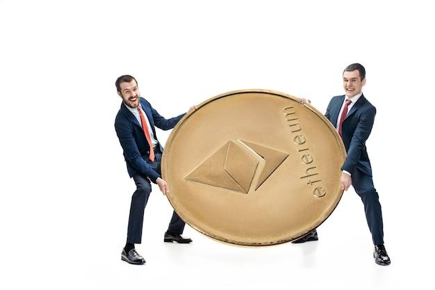 Dos hombres de negocios que sostienen el icono del negocio - ethereum grande aislado en el fondo blanco. criptomoneda, bitcoun, litecoin, comercio electrónico, concepto de finanzas. collage