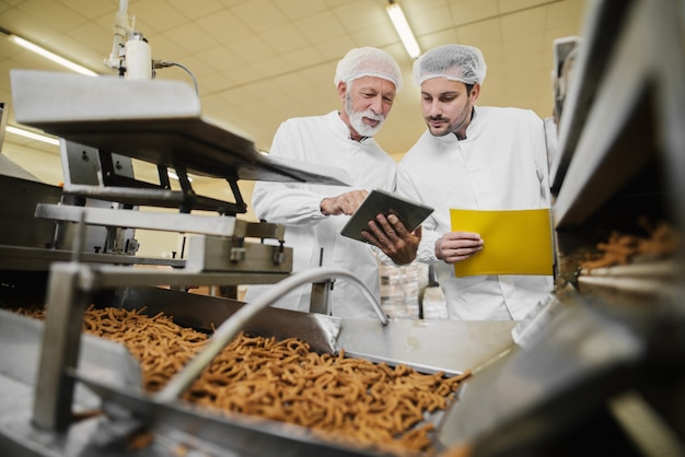 Dos hombres de negocios en ropa estéril de pie en la fábrica de alimentos frente a la línea de producción y mirando y tableta. comprobando la calidad de los productos y hablando.