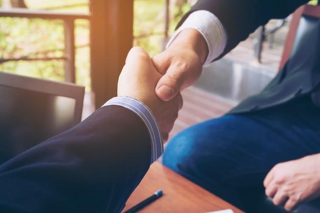 Dos hombres de negocios sacuden la mano en la cafetería