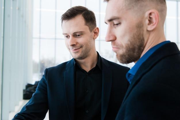 Dos hombres de negocios sonrientes en aeropuerto, discutiendo proyecto importante y mirando la pantalla del teléfono.