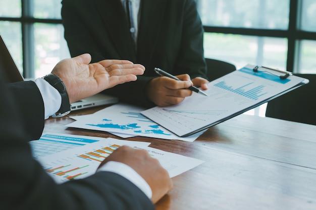 Dos hombres de negocios trabajando juntos y analizando con gráfico de negocios en el escritorio en la sala de reuniones.