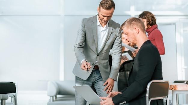 Dos hombres de negocios usando una computadora portátil se están preparando para la próxima reunión