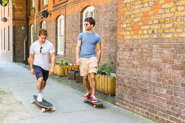 Dos hombres paseando en monopatín por la acera en londres