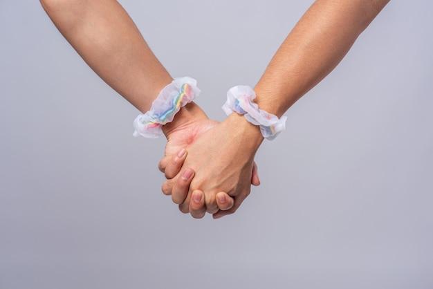 Dos hombres que se aman están cogidos de la mano.