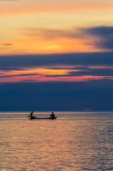 Dos hombres que pescan en el mar bajo puesta del sol.