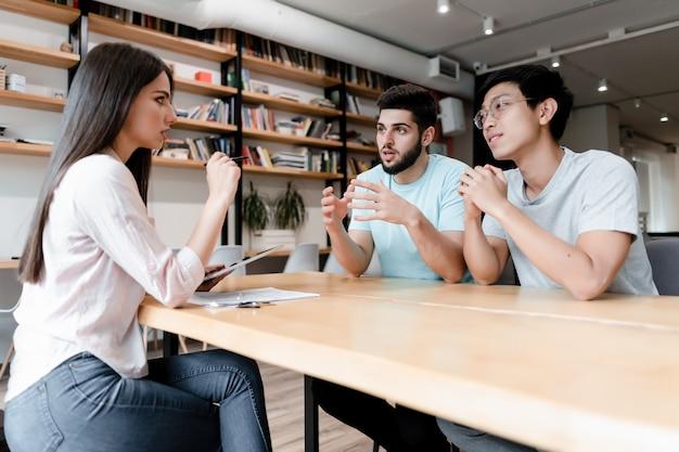 Dos hombres reunidos con una mujer en la oficina