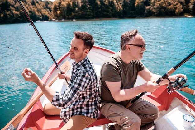 Dos hombres sentados y pescando en canoa.