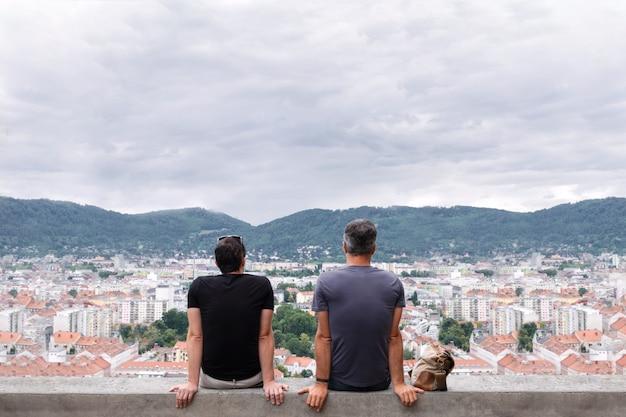 Dos hombres se sientan en el borde de un edificio alto y miran en la distancia a las montañas.