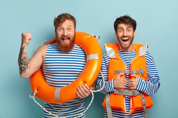 Dos hombres socorristas usan un salvavidas, usan un chaleco naranja especial, miran felices a la cámara