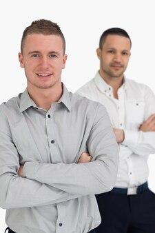 Dos hombres sonriendo mientras cruzan sus brazos