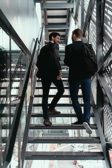 Dos hombres subiendo y bajando escaleras mientras conversan